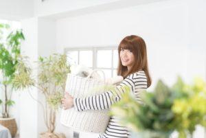 洗濯物を運ぶ笑顔の女性