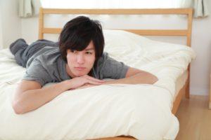 ベッドの上で悩む若い男性