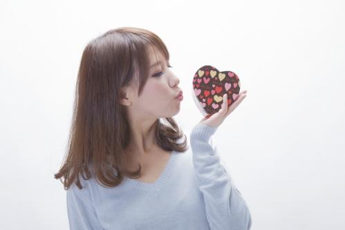 プレゼントを持つ女性(バレンタインのハート型チョコレート)
