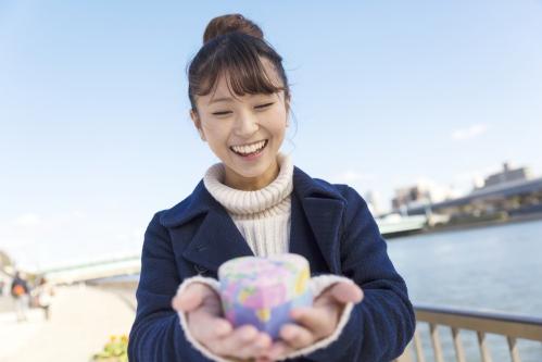 プレゼントを渡す笑顔の若い女性(バレンタインの本命チョコ)
