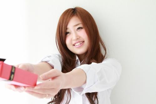 プレゼント(お菓子)を手渡す若い女性(女子高生)