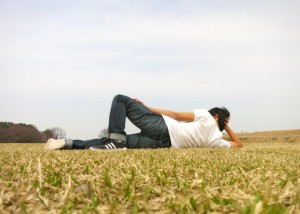 Tシャツを着て芝生の上で寝転ぶ男性