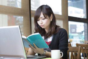 カフェで手帳を見ながら予定の計画を立てる若い女性