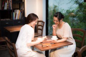 カフェでスマホを見ながらおしゃべりする20代の女性2人組