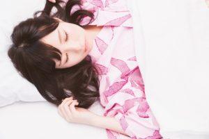 布団の中で眠る女性