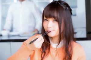 箸を口に運ぶ(食べる)女性