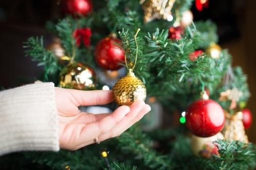 クリスマスツリーの飾りつけをする手