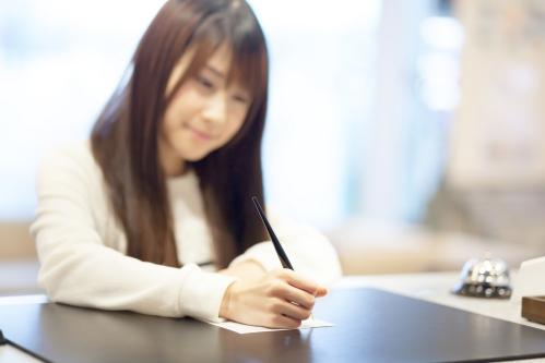 受付で自分の名前を書く女性