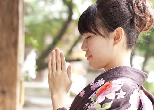 神社でお参り(参拝)する女性