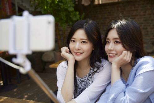 自撮り棒を使って写真を撮る女子2人組
