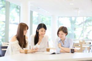 カフェでおしゃべりする3人の女性(女子大生・大学生)