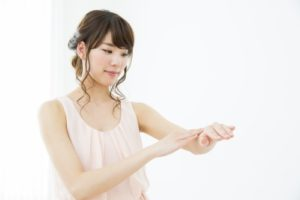 クリームを手に塗る若い女性