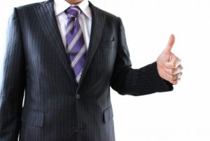 スーツでグーサインをする男性