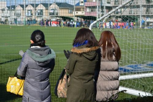 冬に少年サッカーの応援をするママたち