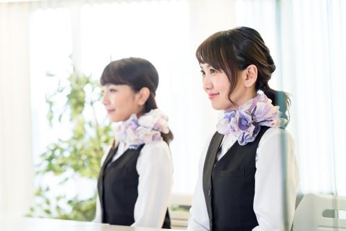 銀行の窓口に立つ笑顔の女性行員2人
