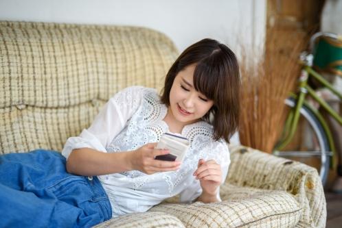 ソファーの上で寝ころびながらスマホでネットショッピングを楽しむ女性