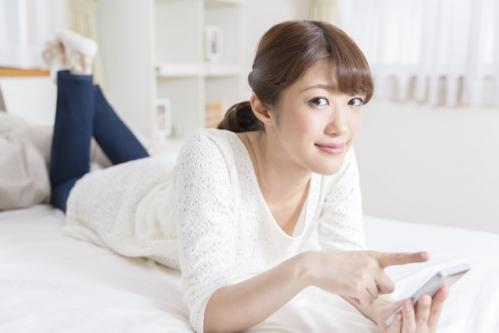 部屋の中で寝ころびながらスマホを使ってネットショッピングを楽しむ女性03