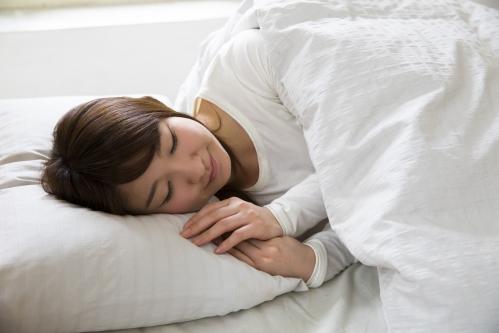 ベッド(布団)で寝る女性