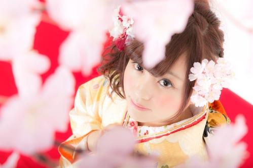桜を見上げる振り袖姿の女性