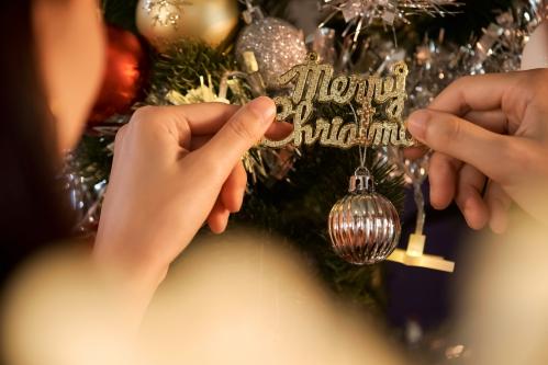 クリスマスツリーの飾り付けをする家族(手)