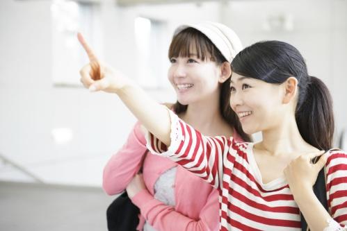駅構内を歩く女性2人組(指をさしながら・旅行)