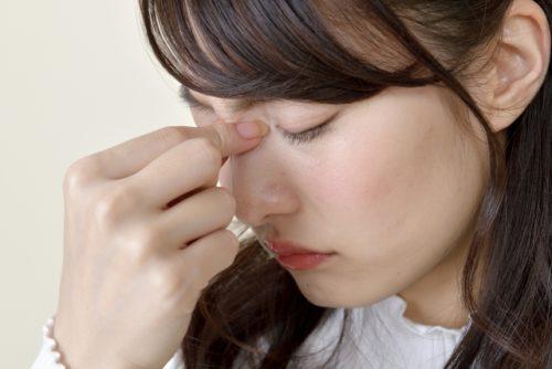 眉間を押さえる女性(頭痛)