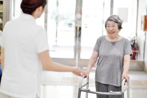 歩行器を使うおばあちゃんと介護士(リハビリテーション)
