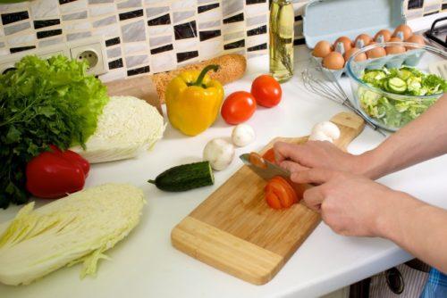 トマトを切るグレーシャツの外国人男性の手