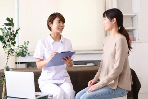 白衣の女性(医療従事者)とカウンセリングをうける女性(患者)